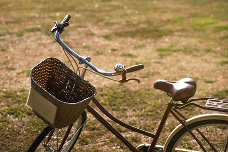 Close-up of bycicle with basket standing on ground. Easy transport for riding during travelling or vacation