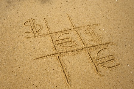 Tic-tac-toe game with playing euro and dollar symbols on sand. Concept of financial currency games Stock Photo