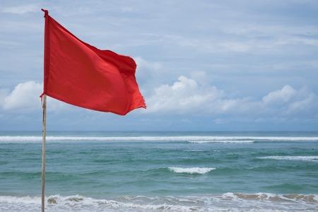 Een rode waarschuwingsvlag op het strand in Nuca Dua Bali, Indonesië. Gevaar om te zwemmen in de oceaan Stockfoto - 92321016
