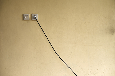 Power socket with plugged electric cable through the wall. Inconvenient location of electricity at home.