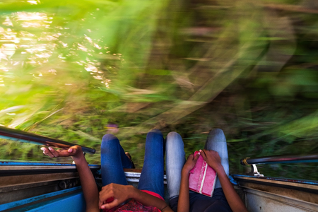 Traveling in Sri Lanka train. Legs of passengers and motioned green land. View from top to down