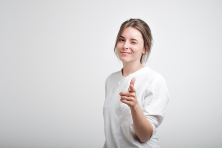 Positive cheerful young caucasian woman wearing white casual T-shirt blinking her eyes and smiling pointing at camera with index fingers. Facial emotion. Succees in life or studies
