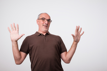 European italian man in a panic mood waving his arms. In brown shirt and glasses. Concept of unexpected news