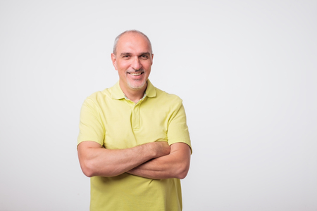 portrait of italian mature man in yellow shirt. He is standing condident on gray background. 版權商用圖片