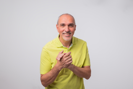 portrait of italian mature man in yellow shirt. He is standing confident on gray background.