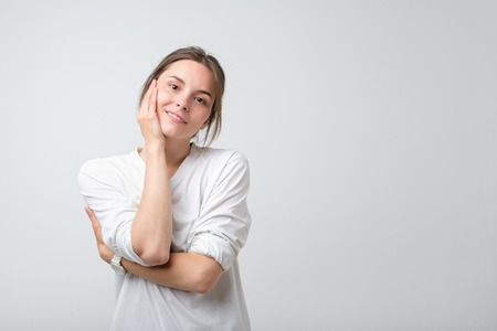 Portrait of young beautiful caucasian woman in white t-shirt cheerfuly smiling looking at camera. Studio photo isolated on white background. Copy space.