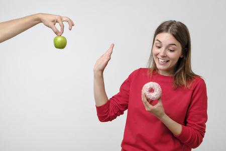 Konzept für gesunde Ernährung und Ernährung. Schöne junge Frau, die zwischen Früchten und Bonbons wählt. Sie bevorzugt einen rosa Donut anstelle von grünem Apfel Standard-Bild