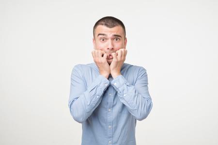 Portrait jeune homme anxieux en chemise bleue se ronger les ongles les doigts paniqués. Il a peur d'entendre les résultats des examens ou des nouvelles.