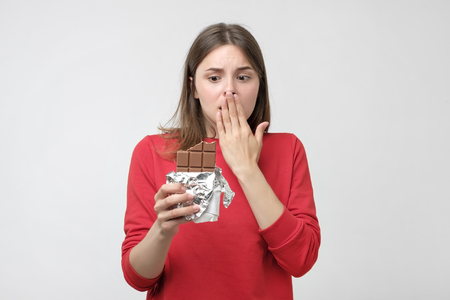Portrait sad young woman in red sweater tired of diet restrictions. She want to eat chocolate isolated on gray wall background. Human face expression emotion. Nutrition concept.