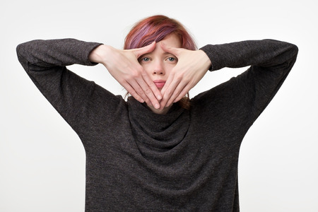 Anonymous concept. Young woman with interesting colorful hairstyle hiding her face with hand.