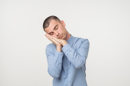 Young man wearing a blue shirt outfit putting his palms like a pillow. Looking sleepy and tired. No energy concept