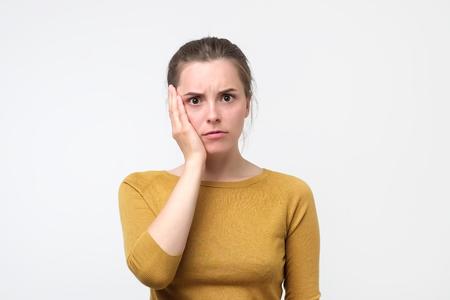 黄色いセーターを着た若いヨーロッパ人女性が歯の痛みを感じている。頬の近くに手を握っているティーンエイジャー。