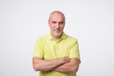 Portrait of mature sad man in yellow t-shirt. He had bad mood. Concept of negative emotion, facial expression