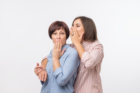 Women mother and daughter gossiping and telling a secret isolated over gray background