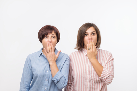 Portrait of a two surprised women mature mother and daughter standing over gray background and looking at camera. They are shocked of news and covering their mouths with plams