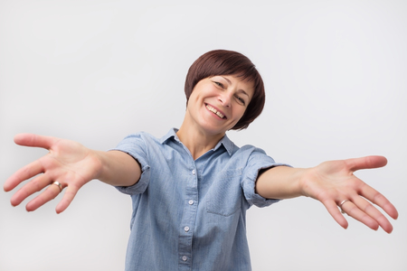 Portrait of attractive mature woman raised up arms hands at you. She is dressed in blue shirt. Happy to welcome a friend or guest