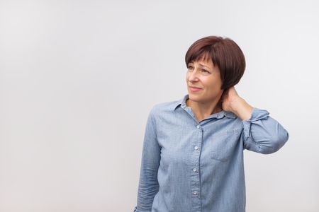 Closeup portrait of worried mature good looking woman standing on grey wall background with copy space. Negative human emotion facial expression Stock Photo