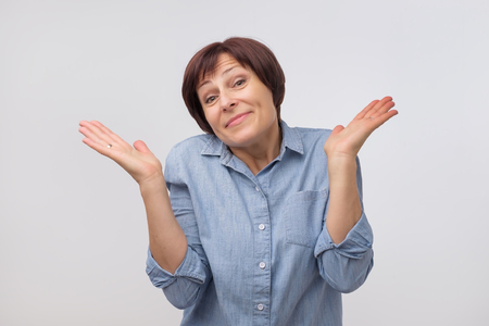 Shrugging mature woman in doubt looking at camera. Attractive confused female gesturing do not know sign on gray background