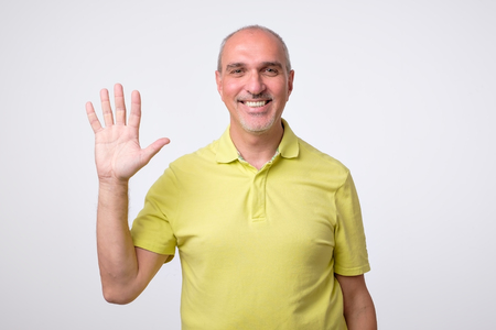 Friendly-looking attractive european man waiving hand in hello gesture while smiling cheerfully. Host is glad to welcome his guests or friends