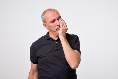 Closeup portrait of mature man wearing black shirt with tooth ache isolated on gray background. Concept of dental problems and healthcare