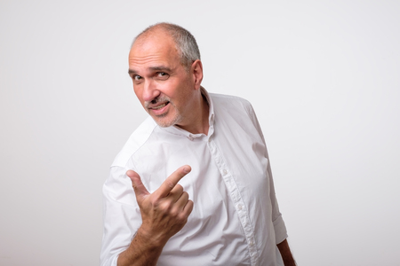 Mature hispanic man pointing with finger while arguing with his opponent. He is not agree with arguments.