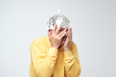 Caucasian mature man in a tin foil hat displeased closing his face with hands. Afraid of radiation or aliens