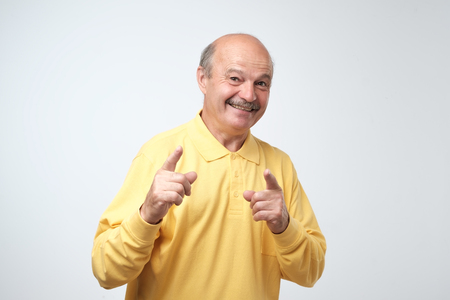 Portrait of attractive senior man pointing with forefingers at you, smiles broadly with teeth, dressed in casual yellow t-shirt, isolated against gray wall. Positive emotions