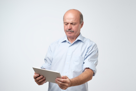 Mature european man using a digital tablet. He is puzzled and confused. He did not know how to use his new gadget