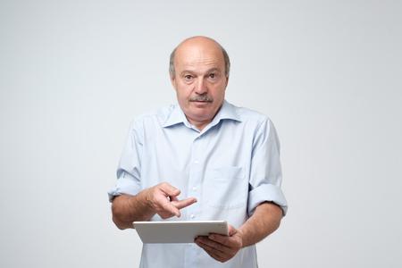 Hombre europeo maduro que usa una tableta digital. Está perplejo y confundido. No sabía cómo usar su nuevo gadget. Foto de archivo