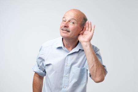 Porträt des älteren lässigen Mannes, der Konversation über weißem Hintergrund belauscht. Sprechen Sie bitte laut Konzept. Was hast du gesagt Standard-Bild
