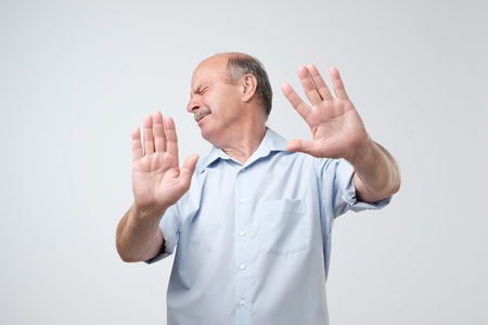 Displeased mature man refusing, stretching hands to camera over grey background. I do not want to have deal with you concept