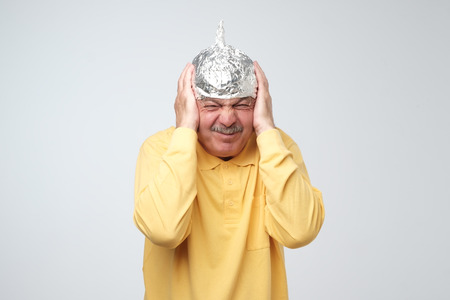Caucasian mature man in a tin foil hat displeased hiding from outdoor life. Afraid of radiation, loud sounds or aliens