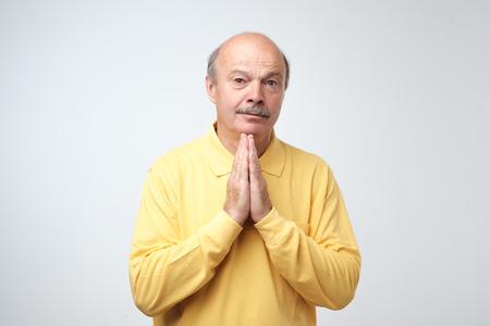 Closeup portrait d'homme mûr désespéré en chemise jaune montrant les mains jointes, demandant de l'aide ou une excuse. Veuillez me pardonner concept