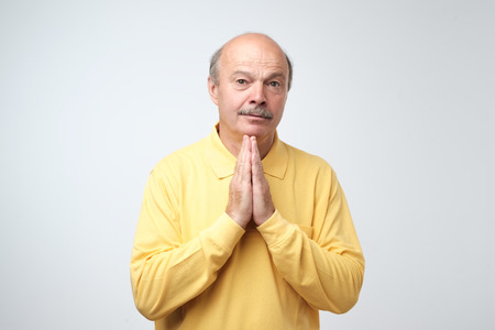 Closeup portrait of desperate mature man in yellow shirt showing clasped hands,asking for help or excuse. Please forgive me concept Standard-Bild - 106220783