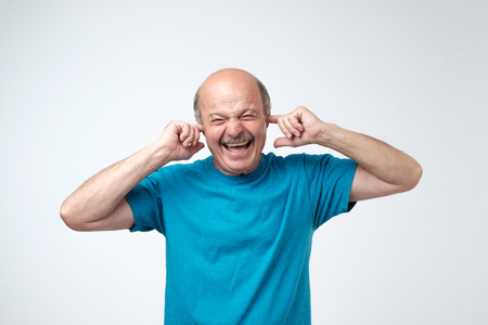Using natural earplugs not to hear spoilers. Good-looking happy mature european man smiling with closed eyes, holding index fingers in ears, waiting for surprise