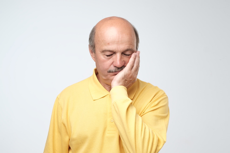Closeup portrait of upset worried sad, depressed, tired business man. He is very stressed holding hand on head, isolated on white background. Negative human emotion facial expression