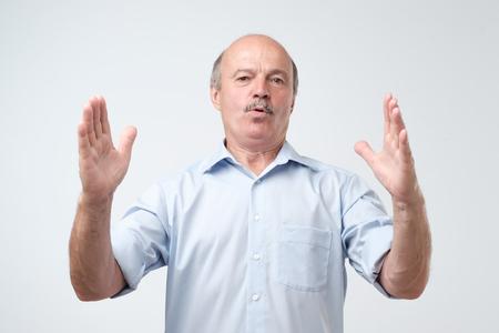 Hübscher reifer Mann, der mit Händen gestikuliert, die großes und großes Zeichen zeigen, messen Symbol. Messkonzept.