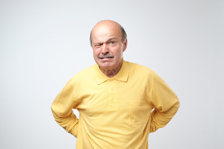 Mature man in yellow t-shirt with nervous crisis isolated on white background