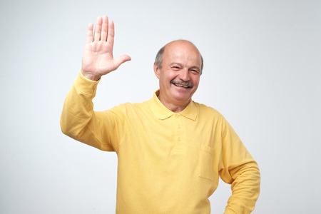 Friendly-looking attractive european pensioner in yellow t-shirt waives hand in hello gesture while smiling cheerfully. Grandfather welcoming his grandson. I am so glad to see you. Stockfoto
