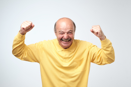 mature hispanic man in yellow shirt celebrating victory of his team over gray background. Football fan concept