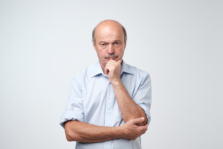 Closeup portrait of sleepy mature man in blue shirt, funny guy placing head on hand, unhappy looking at camera. I am too old for all this deals concept