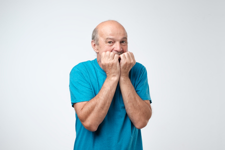Portrait of anxious senior man in blue t-shirt biting his nails fingers freaking out. Im afraid that I will be exposed and someone will know my terrible secret emotion Stok Fotoğraf