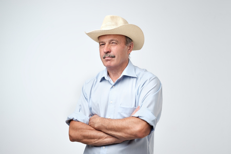 Cowboy style. Mature man adjusting his cowboy hat and looking at camera with distrust while standing against grey background. I do not believe you, you are telling bullshit concept