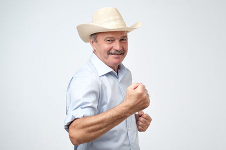 Portrait of handsome successful mature man wearing cowboy hat celebrating his victory holding a fist. He is showing that he is strong despite the fact he is old. isolated on gray background