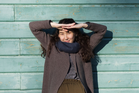 Young asian woman outdoor wearing warm jacket standing near wooden blue wall. Happy mixed race asian caucasian girl in her twenties. Enjoy first sunny day in spring or autumn