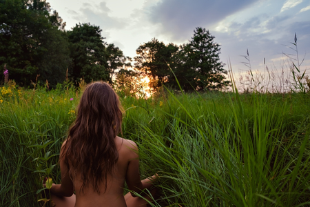 Young brunette woman enjoying meditation on green fresh looking on sunset. Concept of unity with nature