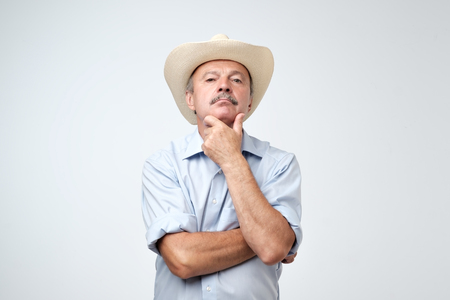 Cowboy style. Mature man adjusting his cowboy hat and looking at camera while standing against grey background