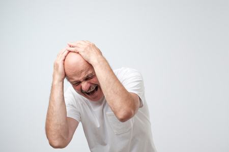 portrait mature hispanic desperate man holding his head in pain standing near a wall