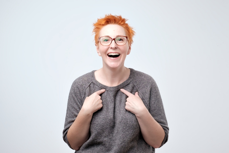 Happy mature woman with red hair pointing fingers at herself. Select me please concept. She can not believe in her luck