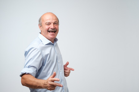 Portrait of very excited mature man, celebrating victory or success. He finally retired and now is free.